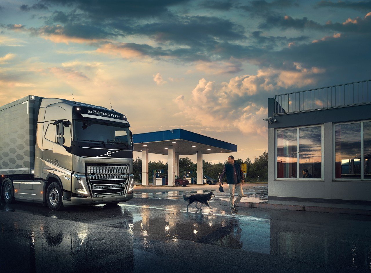 A driver and his dog walk in front of a Volvo truck parked at a gas station
